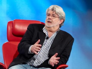 George Lucas doing an interview sitting in a red chair