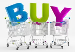 Three shopping carts with large letters BUY to show the Shopping Habits of Wealthy Consumers