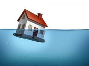 Sinking home and housing crisis with a house in the water on a white background showing the real estate housing concept of flood insurance