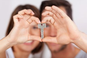 Young couple holding a house key together