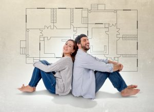 Young attractive couple in love happy together thinking and imaging blueprints , floor plan and design of new house, home, flat or apartment in real state concept to show real estate trends