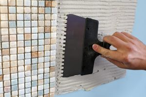 Master Bathroom Renovation: A worker covers the wall with adhesive using a notched trowel.