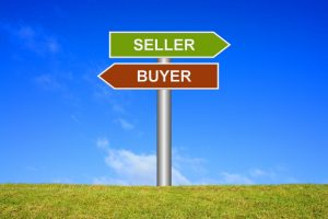 Signpost sign with blue sky and green grass showing seller or buyer to illustrate a buyer's market