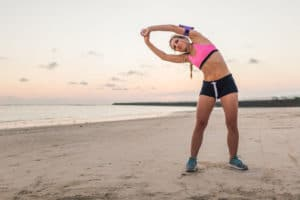 woman stretching at the beach to show interesting financial advice by looking at your health