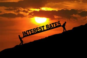 Silhouette of businessmen carrying Interest Rates word uphill to show current mortgage rates