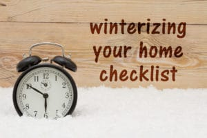 Prepare for winter message, Some snow and an alarm clock on weathered wood with text Winterize your home checklist