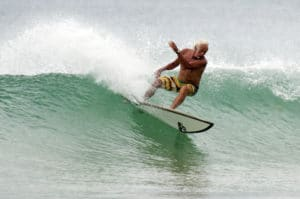 An old man wave surfing to show how important exercise is for those aging at home