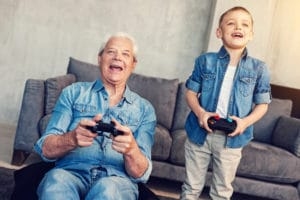 Aging at home. Cheerful happy emotional moment of two relatives playing wonderful games at home