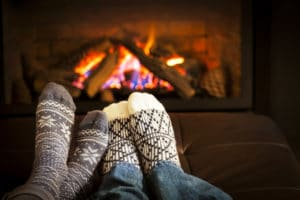 Feet in wool socks warming by cozy fire to illustrate creating a cozy home