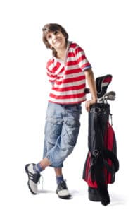 Little boy smiling leaning on golf back, isolated on white