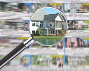 Magnifying glass showing homes for sale to illustrate the importance of real estate disclosure forms