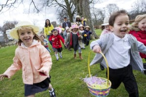 Nursery children running across a field during their outdoor Easter egg hunt, they are wearing handmade hats and carrying baskets to illustrate Easter in Santa Barbara 2019