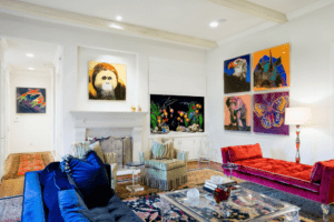 Livng room of an upscale home with a home aquarium on the wall next to other works of art.