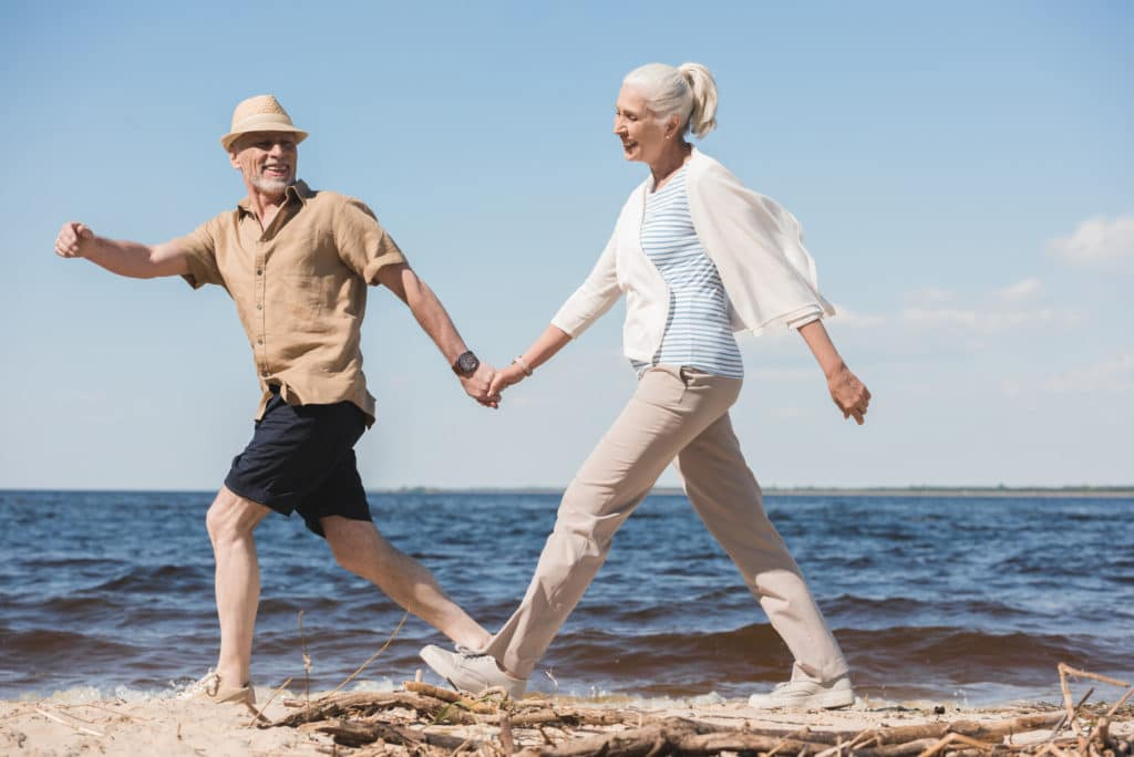 Senior couple holding hands while walking on the beach to illustrate downsizing for seniors