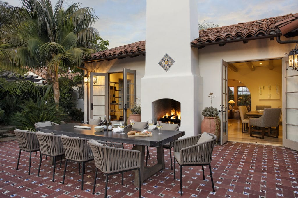 Beautiful red tiled patio with table and chairs and a wood fireplace in the backyard of this Montecito luxury home for sale