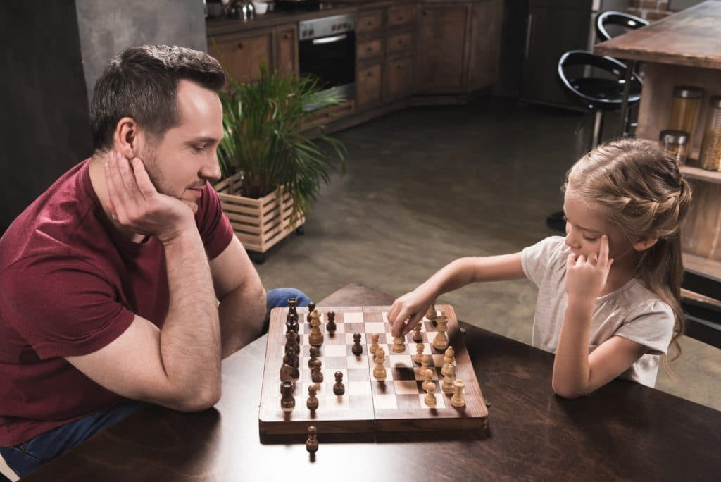 Father and daughter playing chess together while they  are confined in their home
