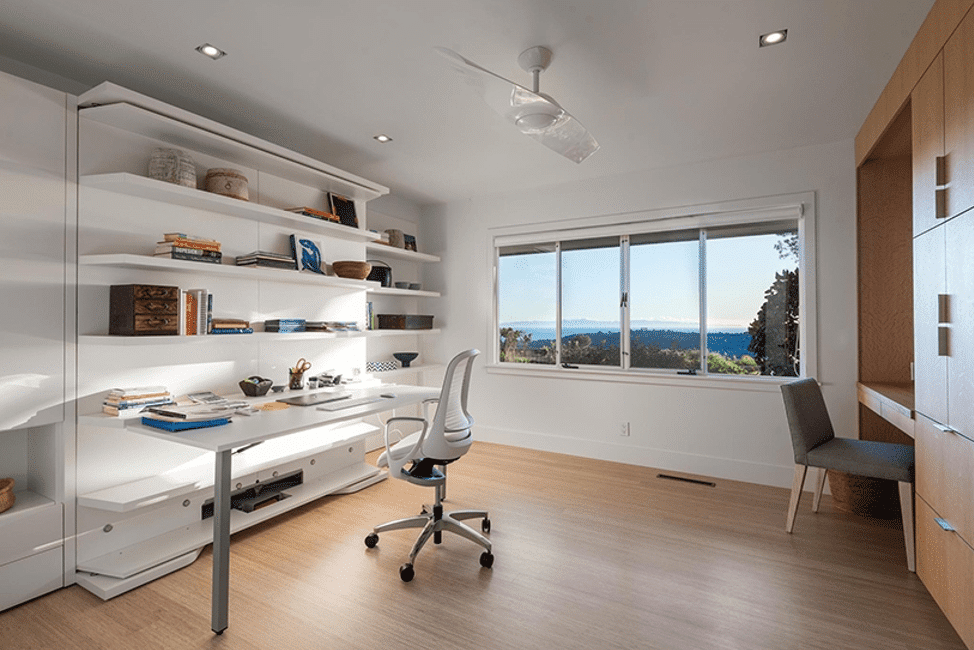 Windows frame a beautiful home office complete with built in shelves and wood floors.