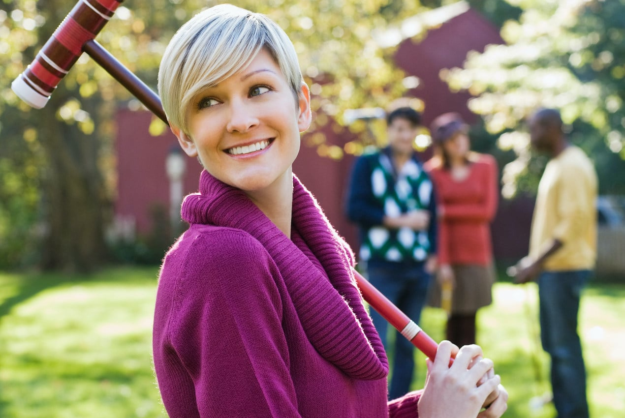 Young woman with croquet mallet to illustrate the many lawn games for your backyard