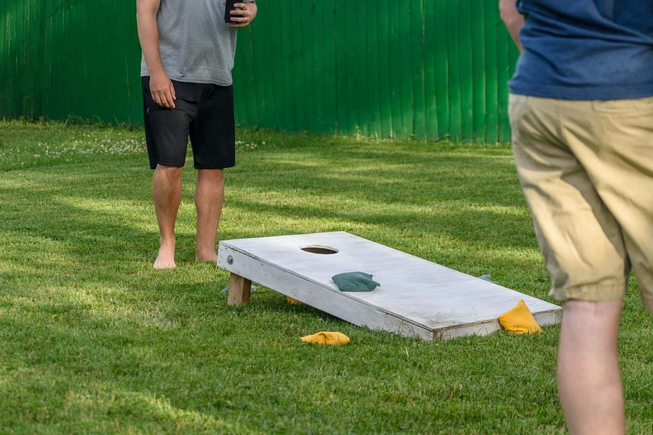 Twopeople playing cornhole in their backyard
