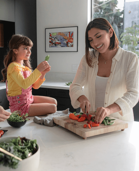a cute little girl sitting on a counter while her mother chops vegetables in their kitchen