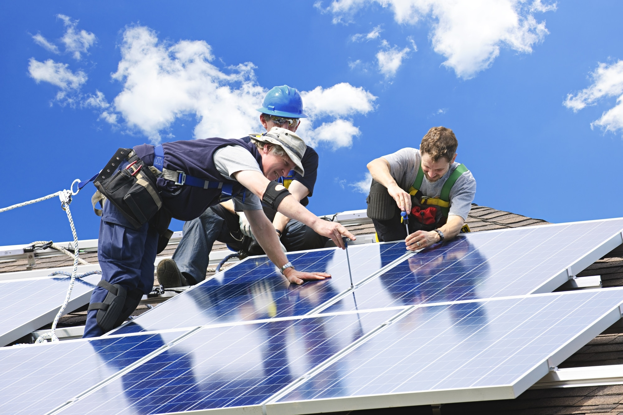 Workers installing alternative energy photovoltaic solar panels on roof