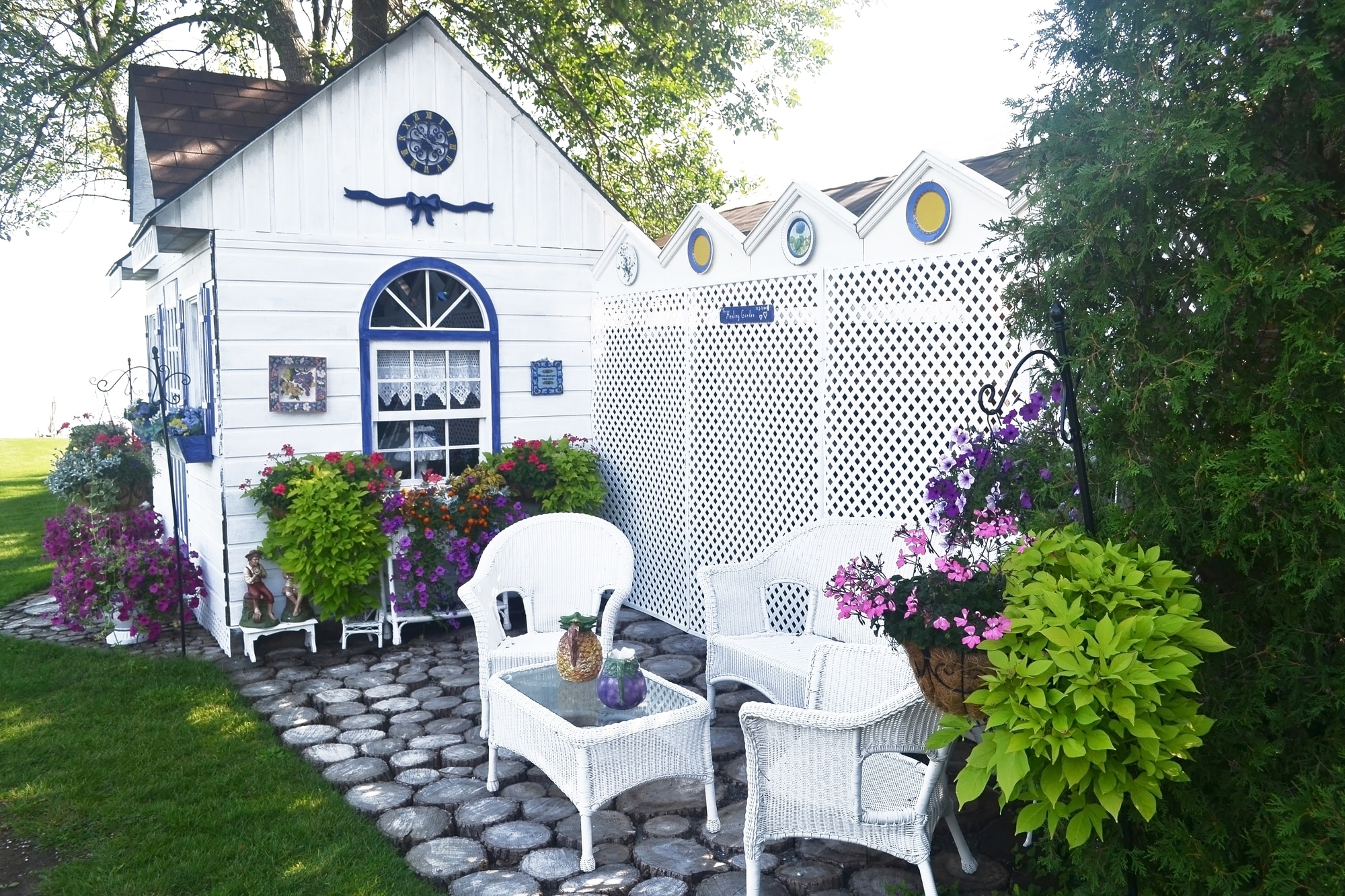 A beautiful small shed with nice chairs and a lot of flowers in the backyard, painted new in white.