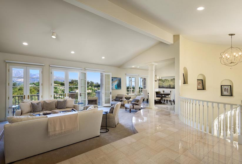 The living room of a luxury condo for sale with windows overlooking the ocean