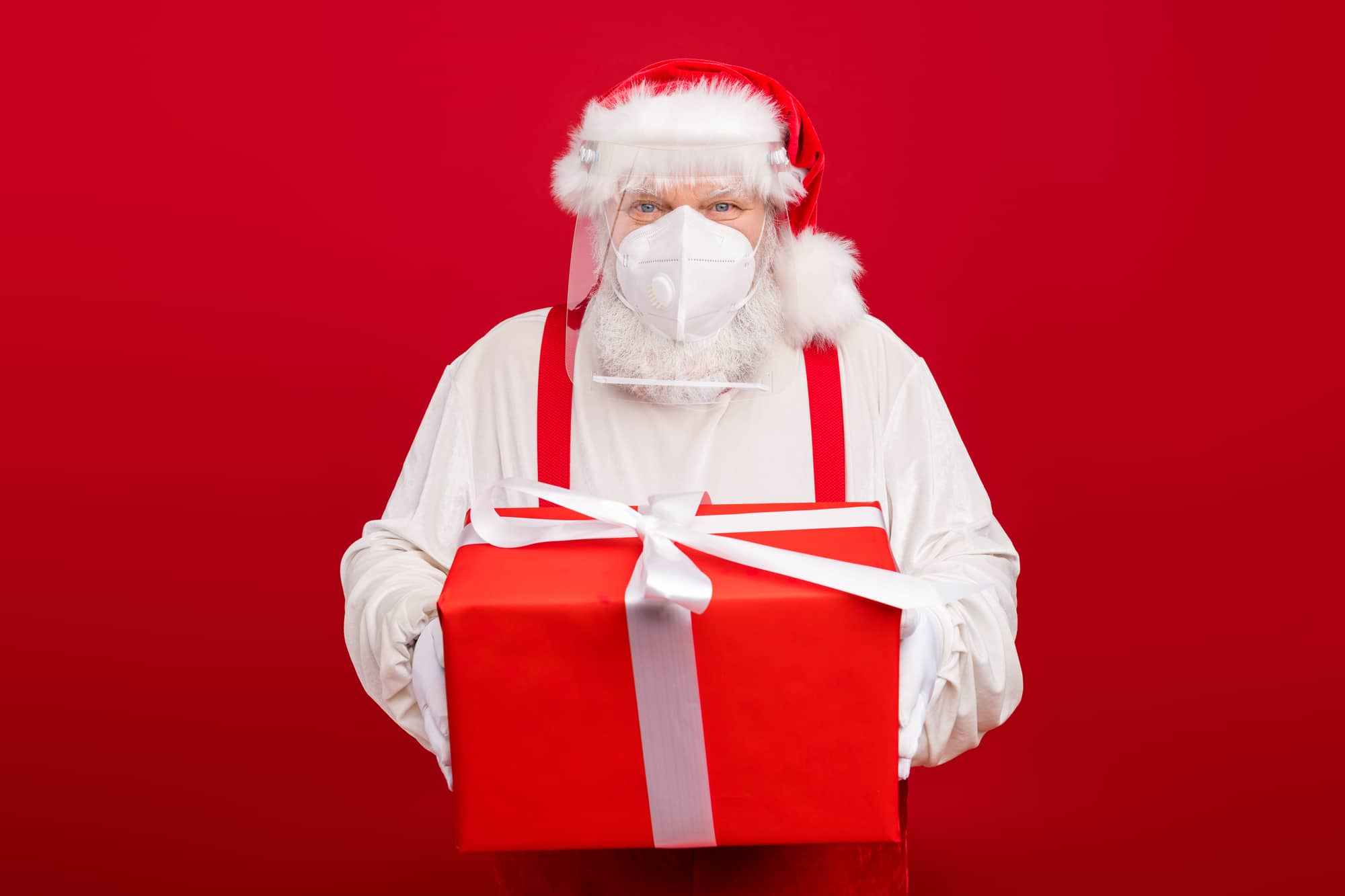 Photo of old bearded merry santa worker distance work take clients, order big gift box delivery home holiday wear protect plastic shield face mask hat shirt suspenders isolated red background